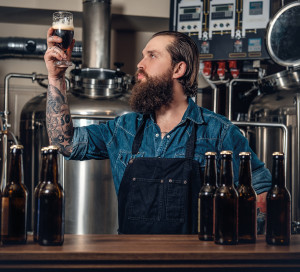 Portrait,Of,Tattooed,,Bearded,Hipster,Male,Manufacturer,Tasting,Beer,In